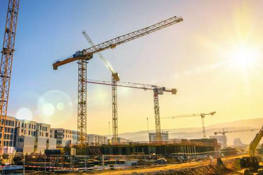 Large construction site including several cranes working on a building complex, with clear blue sky and the sun Bild: Fotolia/Smileus
