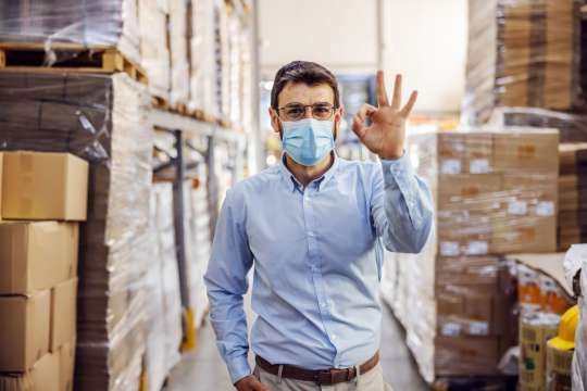 Young businessman with sterile protective mask on standing in warehouse and showing okay sign. Protection from corona virus/ covid-19. Bild: dusanpetkovic1/stock.adobe.com