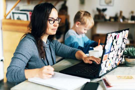 Concept of work from home and home family education. Mom and son are sitting at the desk. Business woman works on the Internet in a laptop, a child writes in a notebook. Bild: Adobestock/Ilona