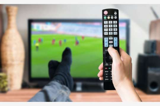 Man is relaxing with legs on table and is watching football match on tv and holds remote controller. Bild: Adobestock/Vchalup