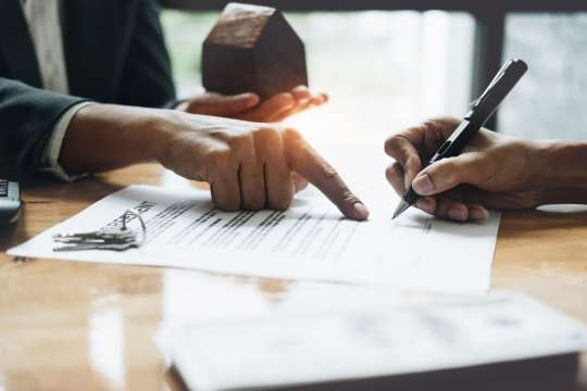 Businessman and estate agent signing a document for house deal, vintage filter effect Bild: AdobeStock/ Natee Meepian